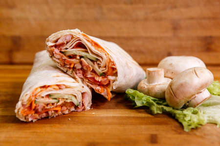 Shawarma sandwich - fresh roll of thin lavash (pita bread) filled with grilled meat, mushrooms, cheese, cabbage, carrots, sauce, green. Traditional Eastern snack. On a wooden background. Stock Photo
