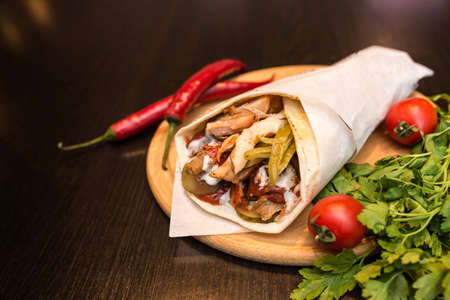 Shawarma sandwich giros - fresh roll of thin lavash (pita bread) filled with grilled meat, mushrooms, cheese, cabbage, carrots, sauce, green. Traditional Eastern snack. On a wooden background. Stockfoto