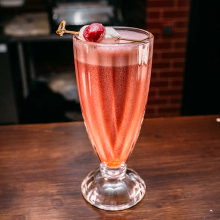 a glass of beautiful bright cocktail on a wooden surface decorated with fruits, berries, leaf of mint and basil at bar counter background. Stock Photo
