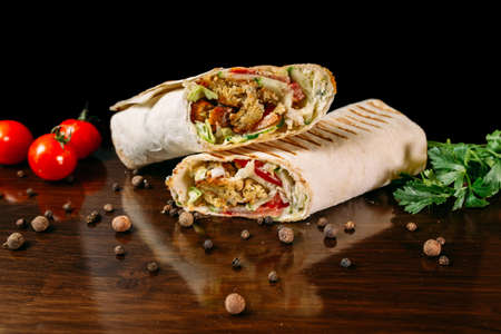 Shawarma sandwich gyro rollo fresco de lavash (pan de pita) pollo ternera shawarma falafel RecipeTin Eatsrellenado con carne a la parrilla, champiñones, queso. Bocadillo tradicional de Oriente Medio. Sobre fondo de madera