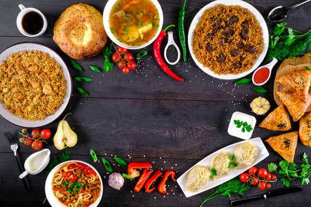 The concept of oriental cuisine. Assorted Uzbek food set, pilaf, samsa, lagman, manta, shurpa Uzbek restaurant concept, Uzbek food. Homemade Uzbek pilaf or plov from lamb served in cast iron cookware.