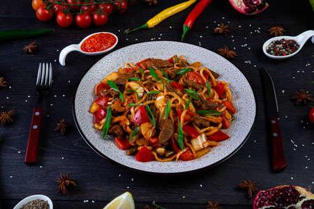 The concept of middle East cuisine. Assorted Uzbek food set, pilaf, samsa, lagman, manti, shurpa eastern restaurant concept, Uzbek food. pilaf or plov from lamb served in cast iron cookware.