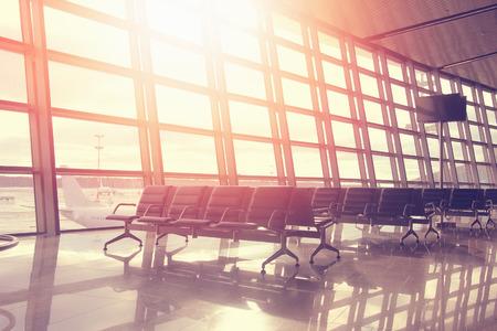 夕暮れの空港で ozhidanidaniya 便の席。カラフルな太陽の光は、赤い色で部屋を満たします。ビジネスや旅行のコンセプトです。近代的な空港ラウンジ。 写真素材 - 73365526