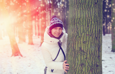 radiantly: Happy girl smiling and peeking out from behind a tree in the forest on a background of a sunset in the winter. Christmas atmosphere, colorful colors of sunlight and radiantly snowflakes. Concept of happiness and freedom.