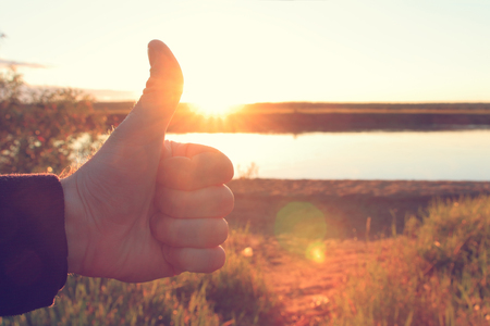 A mans hand holds a thumb up on background of bright sunrise. The concept of success and happiness. Everything will be fine.