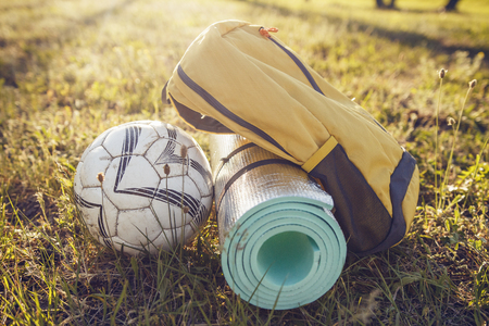 Picnic backpack rug and soccer ball on grass in summer bright sun. Hike in nature outdoors camping macro Stock Photo