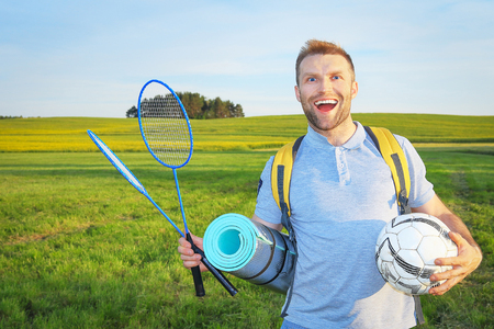 Beauty young man enjoys fun traveling with a backpack  rackets and ball, smiling on  background of green meadows. Relax in nature, actively spend time outdoors, camping and picnic