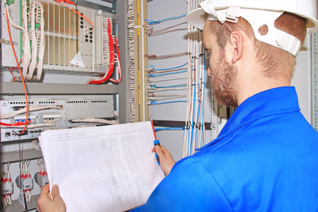 Electrician in white helmet is looking at electrical diagram in control cabinet of industrial equipment. electrical engineer checks  electrical cabinet.