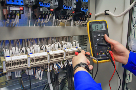In hands of electrician multimeter on background of electric closet close-up. engineer performs adjustment works of the industrial equipment macro.