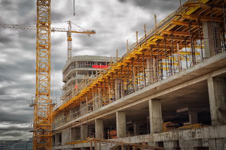 Chantier de construction. Grues de construction, murs en béton monolithiques, coffrages pour béton. Le concept de construction.
