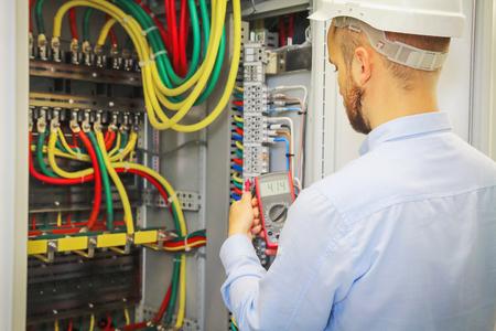 Ingénieur électricien avec multimètre sur fond de coffret de distribution de câbles électriques. Banque d'images - 86306107
