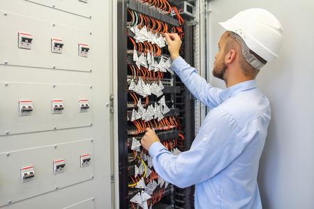 Service Engineer adjusts equipment in data center. Server room of datacenter. Reklamní fotografie
