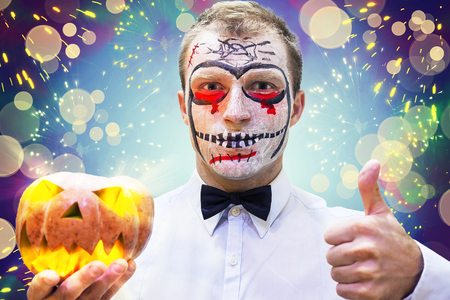 Young man on crazy Halloween party. Portrait of man in mask on holiday Halloween. Blood theme on Halloween. Concept of Halloween party Stock Photo - 87518061