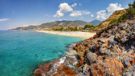 Mountains and seascape on sunny summer day in Alanya, Turkey. Beautiful view on tropical beach and coastline through Turkish rocks