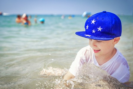 Happy caucasian boy is bathing in sea water on beach against are swimming people on horison. Summer vacation on sunny day. Tropical holidays with childs.