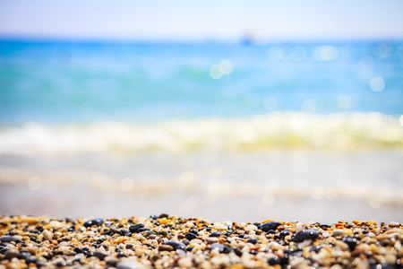 Sea beach background. Beach and blurred blue water with waves on horizon Stock Photo