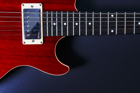 Red electric guitar on black background closeup. Music concept