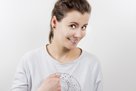 Portrait of girl pointing at herself. Woman is surprised and points to herself with finger. Interrogative expression Stock Photo