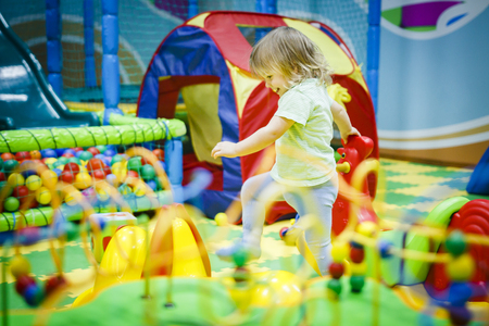 child is playing in the children's room. Children in the entertainment center. Fun in the children's playroom 스톡 콘텐츠
