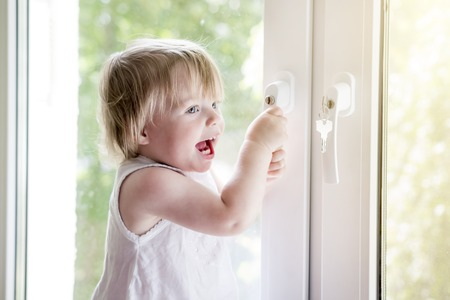 small child near window. lock on handle of window. Childs safety at window. Do not fall out of window. Baby kid opens window Stock Photo