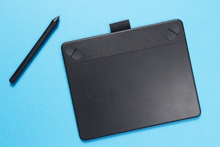 Black graphic tablet with pen on blue background. The designer tool. Banco de Imagens
