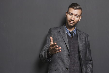 Portrait of stylish handsome man stretching out his hand. confident look of fashionable successful man in gray suit. brutal rich man with an outstretched hand. Elegant businessman with trendy haircut