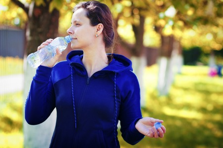girl drinks water from bottle in golden autumn park. woman drinks water after practicing yoga in city park. Rest after workout in the open air