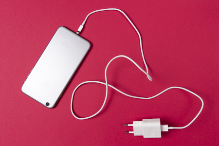 modern smartphone and connected charger cable on pink background