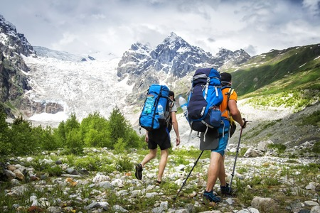 Two hikers with large backpacks in mountains. Tourists hike on rocky mounts. Leisure activity on mountain trek. Adventure of men in wild Svaneti region of Georgia. Groupe Hiking Imagens