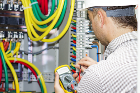 An electrical engineer measures the voltage in the electrical cabinet. A working electrician with a multimeter performs service work