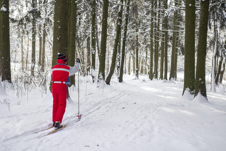 Young guy is skiing in a snowy forest. Active rest in winter. Winter sports. Skier in the woodland Zdjęcie Seryjne