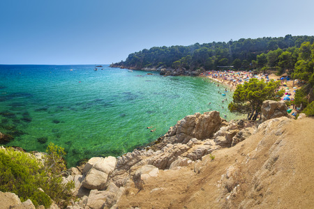 View on Treumal beach in Lloret de Mar, Costa Brava, Spain on sunny summer day. Cala Treumal beach. Vacation on tropical mediterranean sea. Turquoise water, rocks, green plants, clear sky