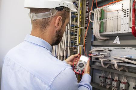 Jonge volwassen elektricien bouwer ingenieur elektrische apparatuur in de zekeringkast van de distributie te inspecteren. Elektrotechnisch ingenieur werknemer in het Configuratiescherm. Onderhoud elektrobox met multimeter. Stockfoto