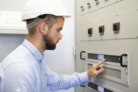 Electrician service man configurates of electrical controller. Maintenance works. Engineering services on industrial complex. Adjustment device. Man adjusts devices. Worker examining equipments
