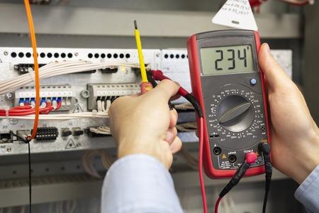 Elektricienmetingen met multimetertester. Mannelijke technicus die zekeringkast met multimetersonde onderzoekt. Close-up van multimeter in handen van ingenieur Stockfoto