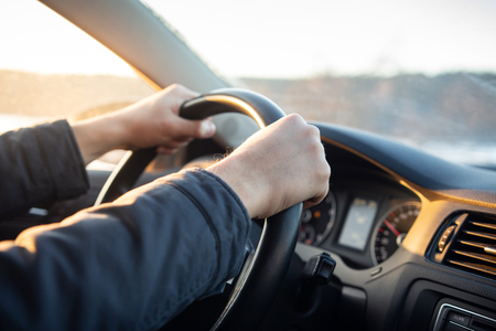 Close-up of driver's hand on steering wheel of car in cabin