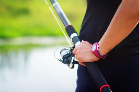 Fisherman with fishing rod close up. Fisherman fishes on lake