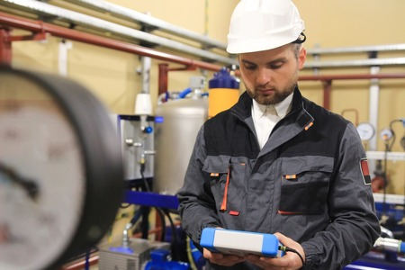 Technician mechanical engineer checking system parameters of centrifugal pump on industrial oil and gas station Zdjęcie Seryjne