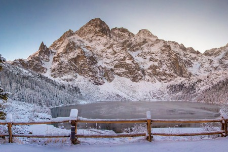Winter landscape of Morskie oko in Tatra national park. Frosty mountains and icy mountain lake in morning