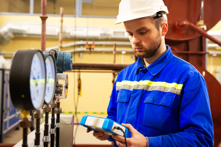Engineer analyzing measurements with pressure manometers on industrial factory. Worker with measure device in hands on gas plant