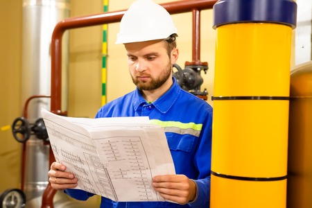 Engineer with drawing on power gas and oil fuel factory. Maintenance work on industrial plant. Worker in helmet