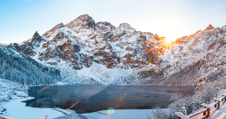 Tatra mountains at winter sunrise. Snowy mountains in sunlight. Winter nature landscape. Morskie oko lake in Tatra. Sea eye lake in mountains, Poland Фото со стока