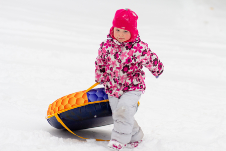Child rolls down snow hill. Winter fun for children. Little girl in winter clothes drags winter sled