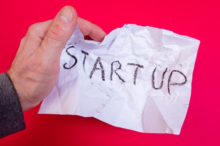 Bad startup strategy. Fail business plan. Hand holds crumpled white paper with strategy word