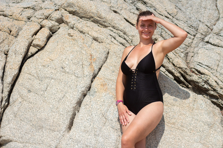 Woman plus size in black swimsuit against rock wall Foto de archivo