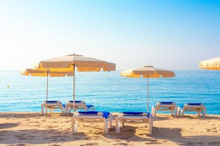 Beach in Lloret de Mar, Spain. Umbrellas and deckchairs on sandy beach in spanish resort in Costa Brava