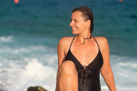 Wet swimming girl on sandy sea beach in swimwear. Smiling woman after bath at sea.
