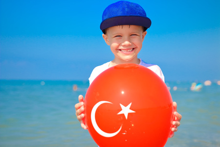 Friendly boy holding balloon with turkish flag on it. Tropical vacation in Turkey. Boy on sea beach