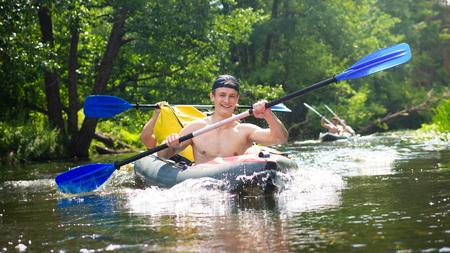 Przyjaciele cieszący się szczęściem podczas spływu po rzece. Faceci w kajaku z wiosłami. Wiosłowanie łodzią w weekend Zdjęcie Seryjne