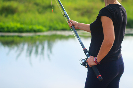 Woman with fishing rod catches fish in lake